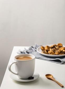 Kaffeetasse auf tisch mit teller mit keksen