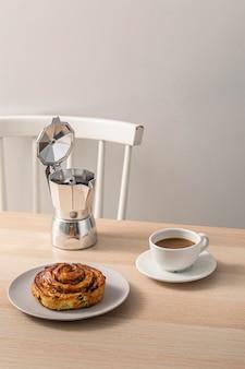 Kaffeetasse auf tisch mit wasserkocher und dessert