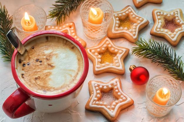 Kaffeetasse auf weißem tisch mit hausgemachten weihnachtsstern-zucker-karamell-keksen