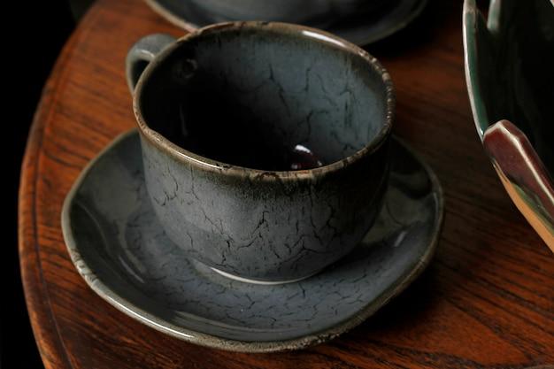 Kaffeetasse aus keramik ist auf einem holztisch platziert.