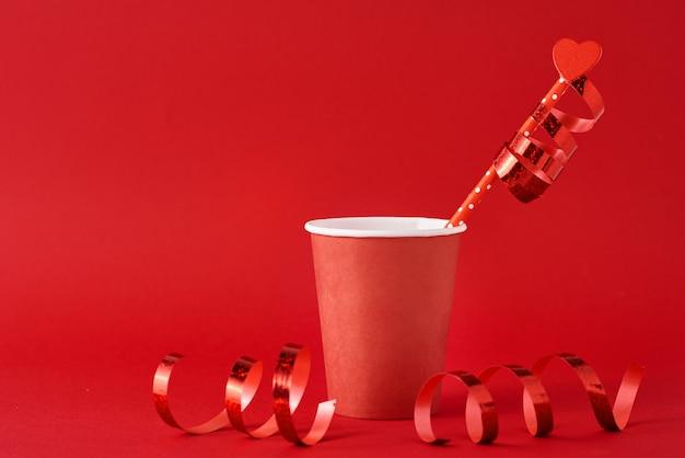 Kaffeetasse aus papier mit holzherz auf stroh und festlichen bändern auf rot. valentinstag konzept