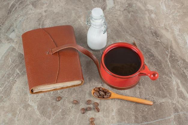 Kaffeetasse, bohnen und notizbuch auf marmoroberfläche