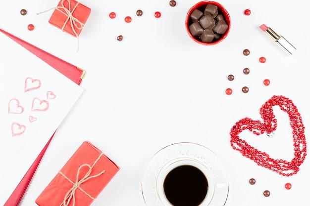 Kaffeetasse, bonbons, lippenstift, herzform und geschenkbox auf weißem hintergrund. valentinstag-konzept-rahmen.