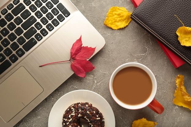 Kaffeetasse, donut und herbstlaub auf grauem hintergrund. herbstkonzept