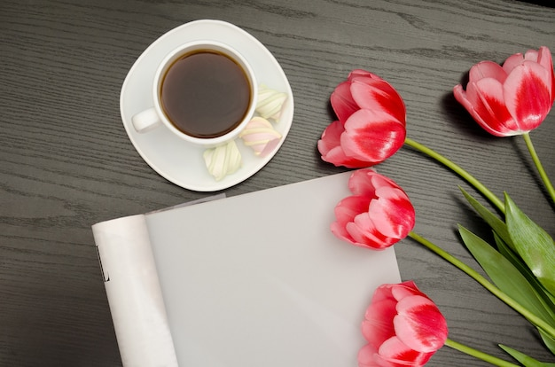 Kaffeetasse, eibisch, leeres blatt und rosa tulpen. schwarzer tisch. ansicht von oben