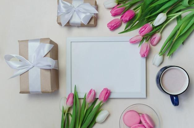 Kaffeetasse, frühlingstulpenblumen und rosa macarons auf pastelltischoberseite ansichtshintergrund
