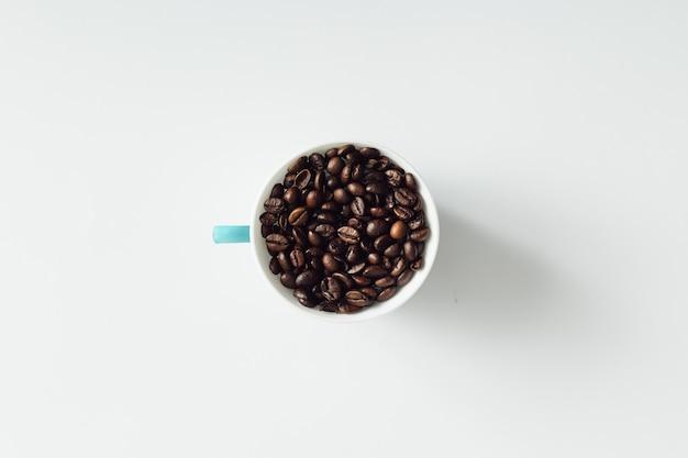 Kaffeetasse gefüllt mit kaffeebohnen auf weißer wand. flach liegen.
