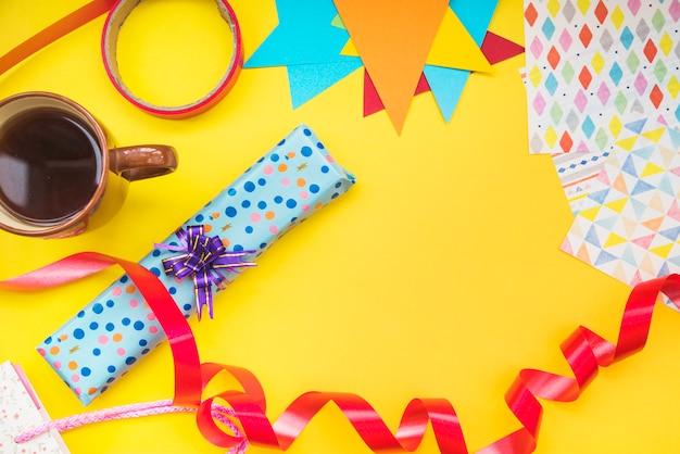Kaffeetasse; geschenkbox; band und eingewickeltes papier auf gelbem hintergrund