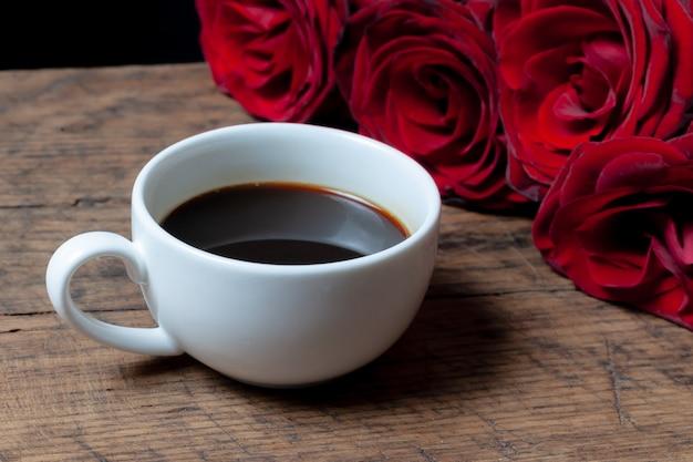 Kaffeetasse, geschenkbox mit rosa band und roten rosen dahinter.