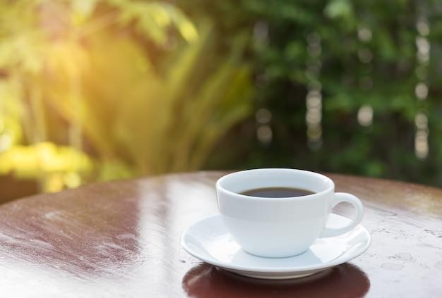 Kaffeetasse im morgensonnenlicht mit grünem gartenhintergrund