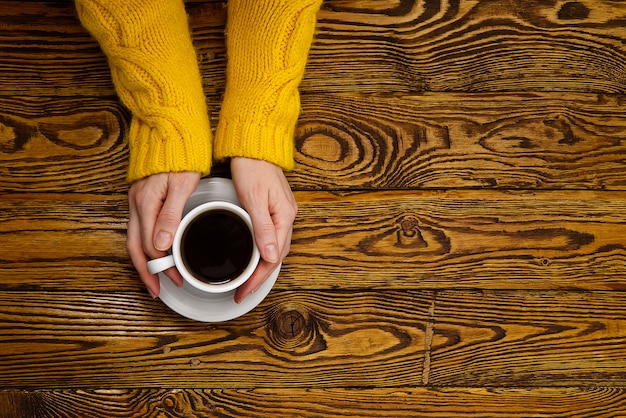 Kaffeetasse in der hand auf alter hölzerner tischoberansicht mit kopienraum. frau im gemütlichen gelben hauptpullover, der eine tasse kaffee hält, während ein getränk genießt