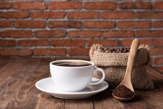Kaffeetasse, kaffeesatz und kaffeebohnen in der leinwand auf hölzerner tabelle mit backsteinmauer
