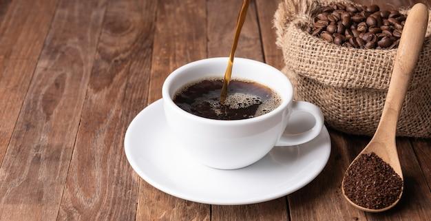Kaffeetasse, kaffeesatz und kaffeebohnen in der leinwand auf hölzerner tabelle