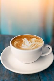 Kaffeetasse latte kunst auf alten vintage blauen holztisch mit kopienraum für text