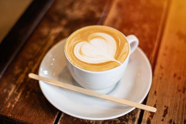 Kaffeetasse lattekunst auf hölzernem hintergrund