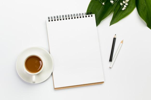 Kaffeetasse, leerer gewundener notizblock und farbige bleistifte mit blättern und blume auf schreibtisch