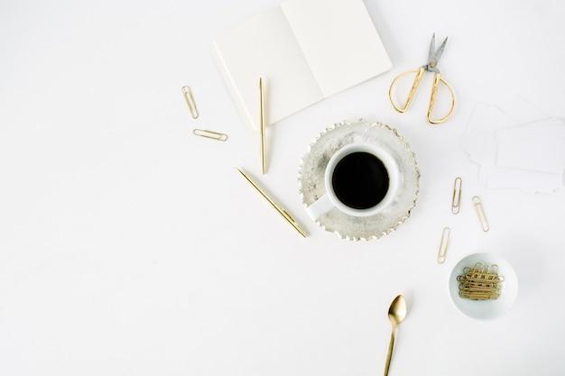 Kaffeetasse, leeres tagebuch und goldenes zubehör: teelöffel, stift, clips und schere auf weiß