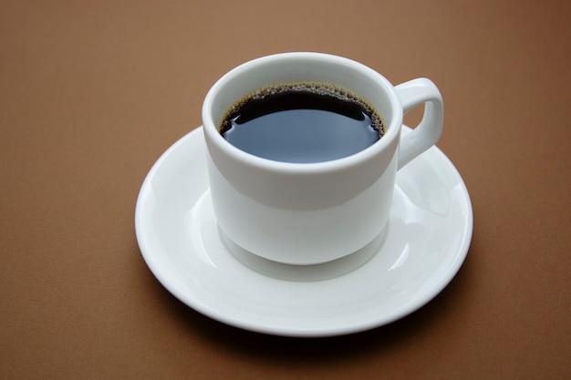 Kaffeetasse lokalisiert auf brauner tabelle. kaffeegetränk mit kopienraum.