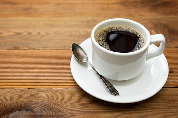 Kaffeetasse lokalisiert auf holztisch. draufsicht, flaches lagekaffeegetränk mit kopienraum.