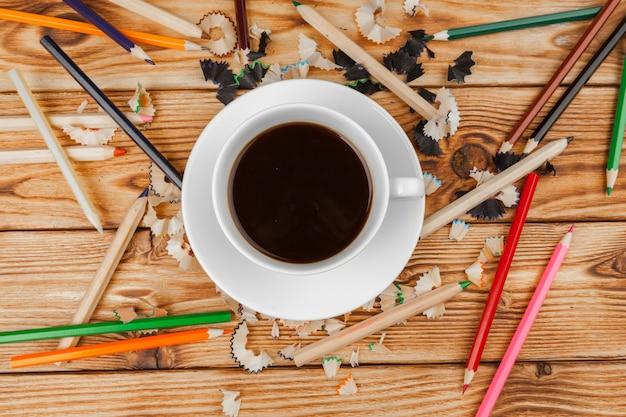 Kaffeetasse mit bleistiften und bleistift schneidet auf hölzernes