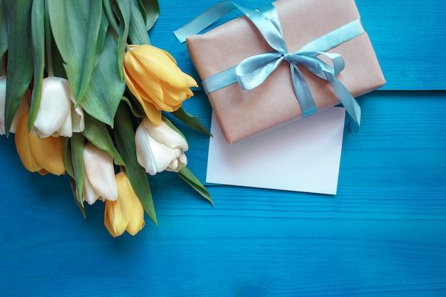 Kaffeetasse mit blumenstrauß von tulpen und geschenk auf rustikaler tabelle des türkises von oben, schönes frühstück, weinlesekarte, draufsicht, ebenenlage