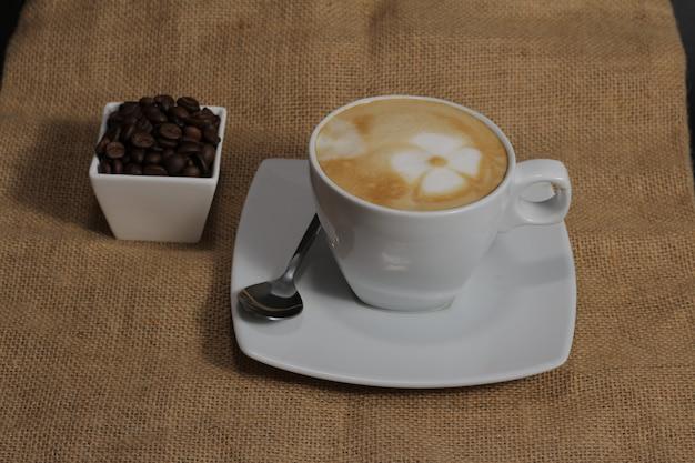 Kaffeetasse mit blumenzeichnung im schaum. draufsicht