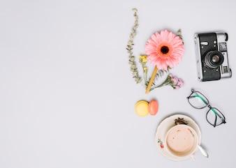 Kaffeetasse mit Blütenknospe, Kamera und Gläsern