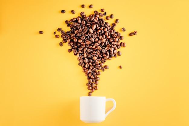 Kaffeetasse mit bohnen auf gelbem hintergrund