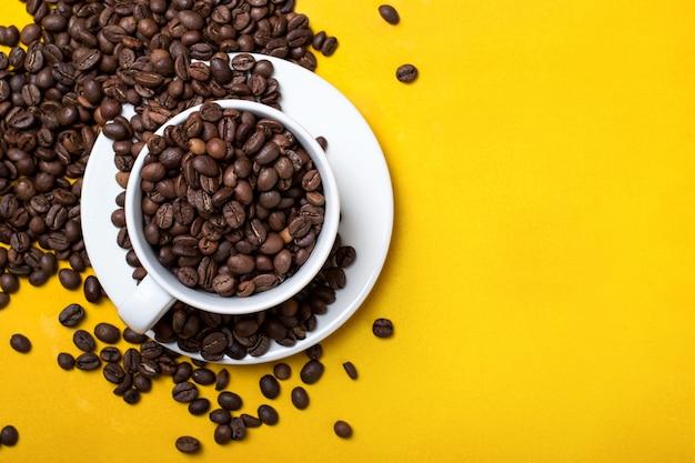 Kaffeetasse mit bohnen auf gelbem tisch