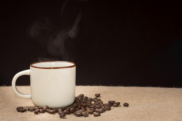 Kaffeetasse mit dampf und kaffeebohnen auf hanfsack