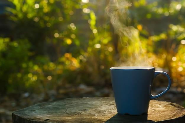 Kaffeetasse mit dem rauch, der auf klotz mit kopienraum gesetzt wird