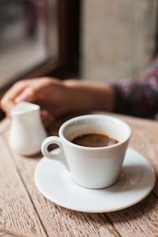 Kaffeetasse mit der defocus frauenhand, die milchkrug im cafã © hält