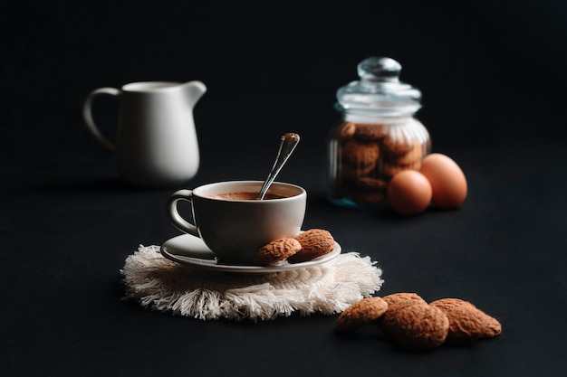 Kaffeetasse mit ein paar keksen in einem glas, milch in einer tasse und eiern.