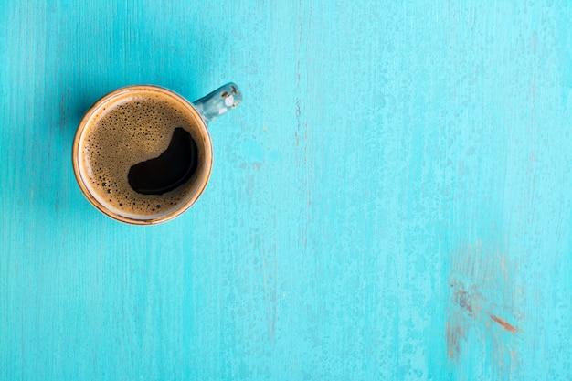 Kaffeetasse mit espresso auf blauem hölzernem hintergrund