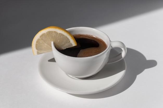 Kaffeetasse mit espresso serviert mit zitrone auf weißem hintergrund mit schatten und sonnenlicht