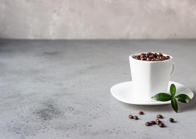 Kaffeetasse mit gerösteten bohnen auf grauem steinhintergrund kopieren sie platz für text