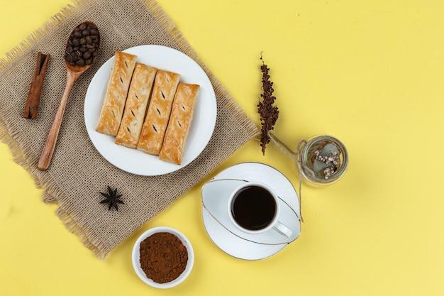 Kaffeetasse mit gewürzen, keksen, getrockneten kräutern und kaffeebohnen