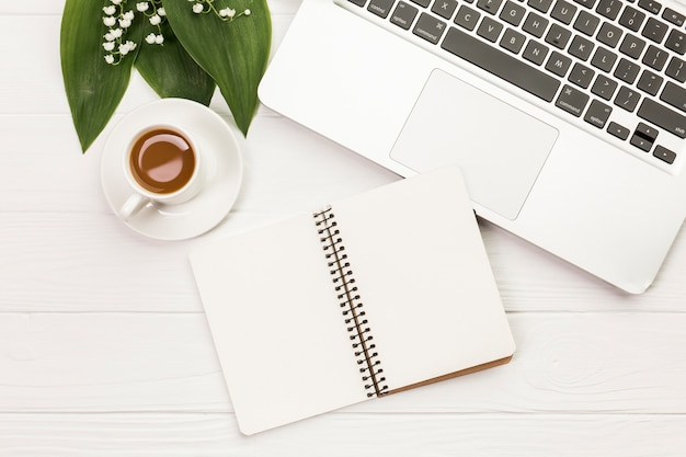 Kaffeetasse mit gewundenem notizblock nahe dem laptop auf weißem hölzernem schreibtisch