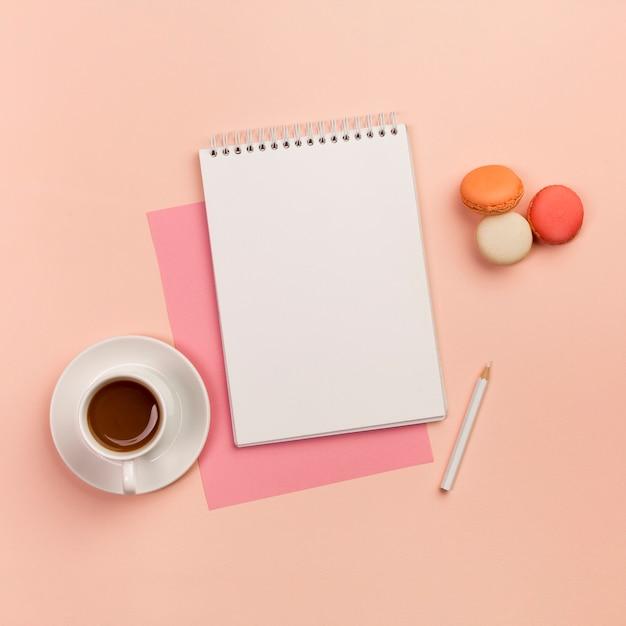 Kaffeetasse mit gewundenem notizblock, weißem bleistift und makronen auf farbigem hintergrund