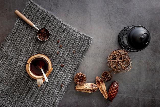 Kaffeetasse mit kaffeebohnen auf einem grauen gestrickten schal