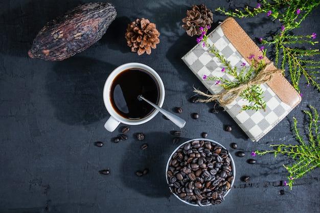 Kaffeetasse mit kaffeebohnen und anmerkungsbuch