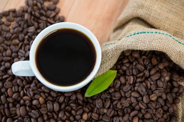 Kaffeetasse mit kaffeebohnen und kaffeeblatt