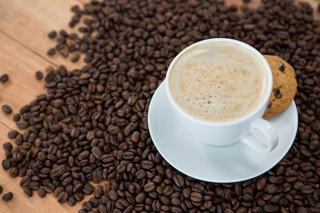 Kaffeetasse mit keks und kaffeebohnen