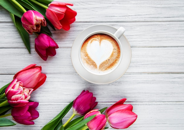 Kaffeetasse mit latte art und rosa tulpen auf dem holztisch. draufsicht, flach liegen.