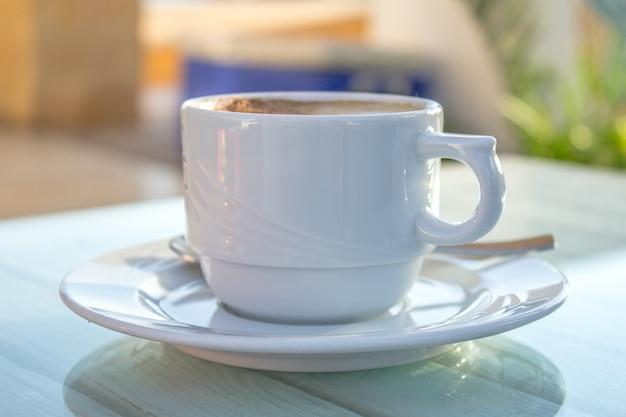 Kaffeetasse mit lattekunst auf hölzerner weißer tabelle.