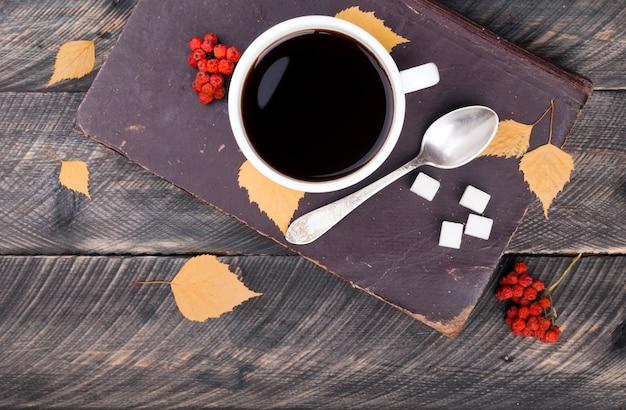 Kaffeetasse mit löffel und zucker, altes buch, herbstlaub und getrocknete eberesche auf hölzernem hintergrund