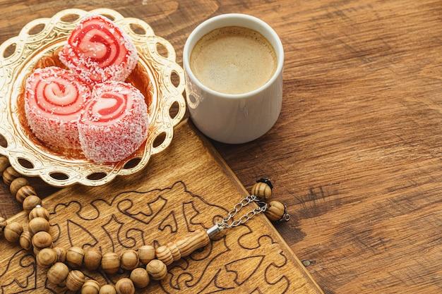 Kaffeetasse mit orientalischen süßigkeiten auf holztisch schließen oben