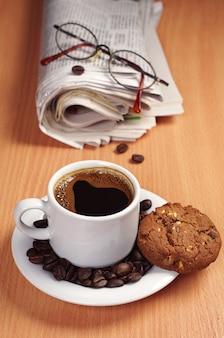 Kaffeetasse mit schokoladenkeks und zeitung auf dem schreibtisch