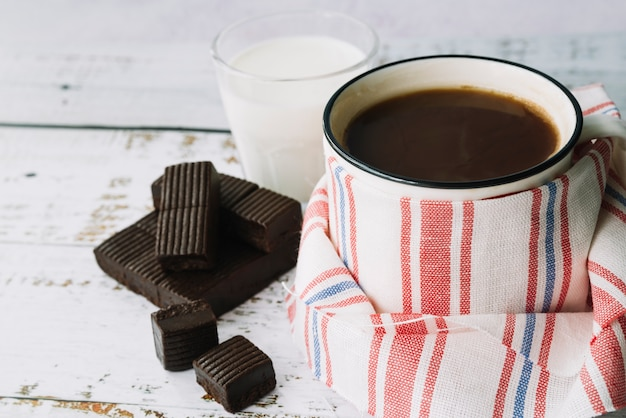 Kaffeetasse mit serviette umwickelt; dunkler schokoriegel und milch auf holztisch