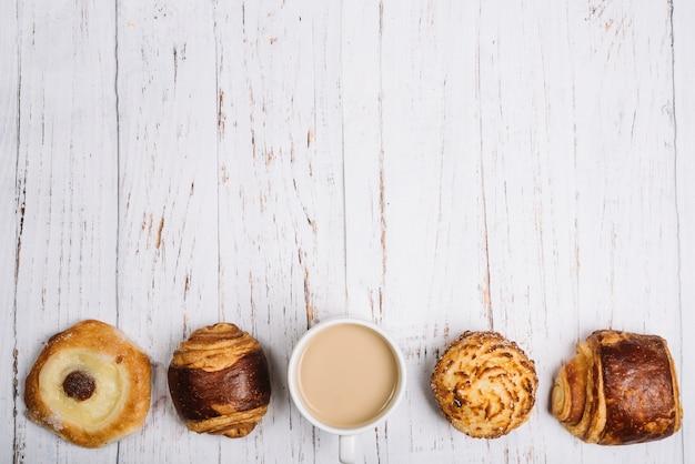 Kaffeetasse mit süßen brötchen auf tabelle